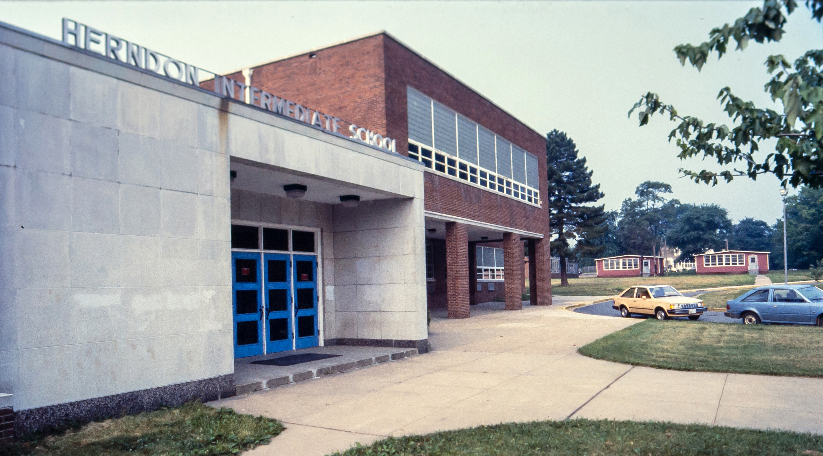 Color photograph of Herndon Middle School taken in the mid-1980s. The old 1927 building has been torn down and two mobile classrooms can be seen in the distance. The main entrance to the building is on the left.