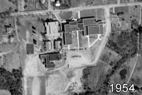 Black and white aerial photograph of Herndon High School taken in 1954. The school has quadrupled in size. There is a large new building on the right and large additions to the gymnasium outbuilding.