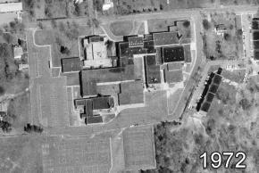 Black and white aerial photograph of Herndon Intermediate School taken in 1972. The old home economics and commercial outbuildings have been torn down and new wing of the building has been added in their place. The old and new buildings are connected by covered walkways.