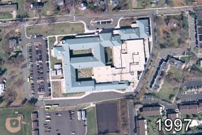 Aerial photograph of Herndon Middle School taken in 1997. A new wing has been built where the old 1927 building was located. The entire building has a new blue / gray colored roof.