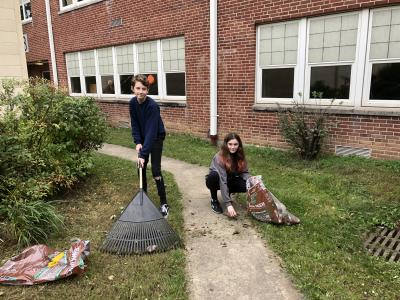 Two student volunteers rake leaves together at the School Clean Up
